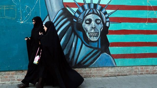 Zwei verhüllte Frauen gehen an einer Wandmalerei der Freiheitsstatue mit Totenkopf vorbei.