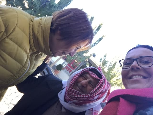 Zwei Frauen lächeln in die Kamera, hinter ihnen ein Mann mit einem Palästinenser-Tuch.
