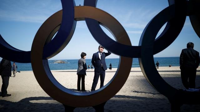 Mann schaut durch Olympiaringe