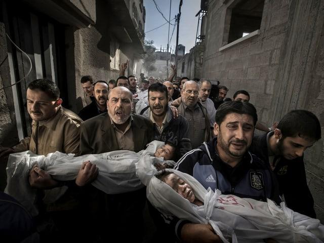 Eine Gruppe trauernder Männer trägt zwei Kinder und deren Vater zu Grabe.