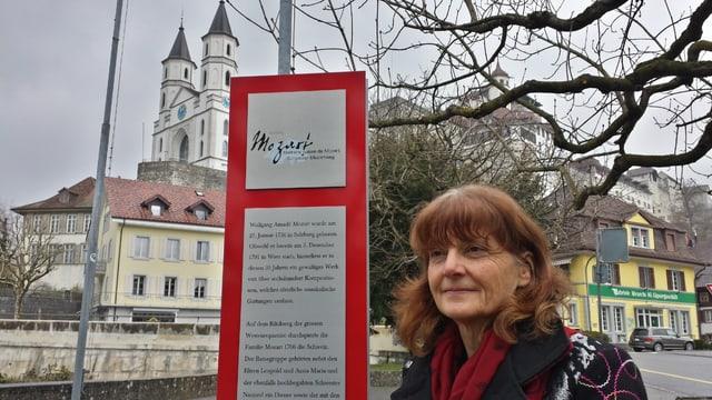 Christina Kunz vor einem Schild des Mozartweges. Im Hintergrund die zwei Türme der Aarburg.