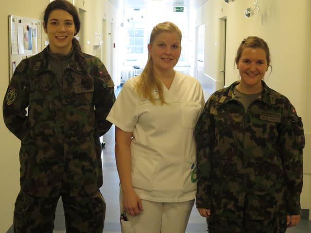 3 Frauen stehen neben einander, zwei im Militärklamotten