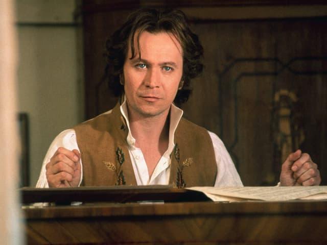 Man mit längeren Haaren sitzt am Klavier
