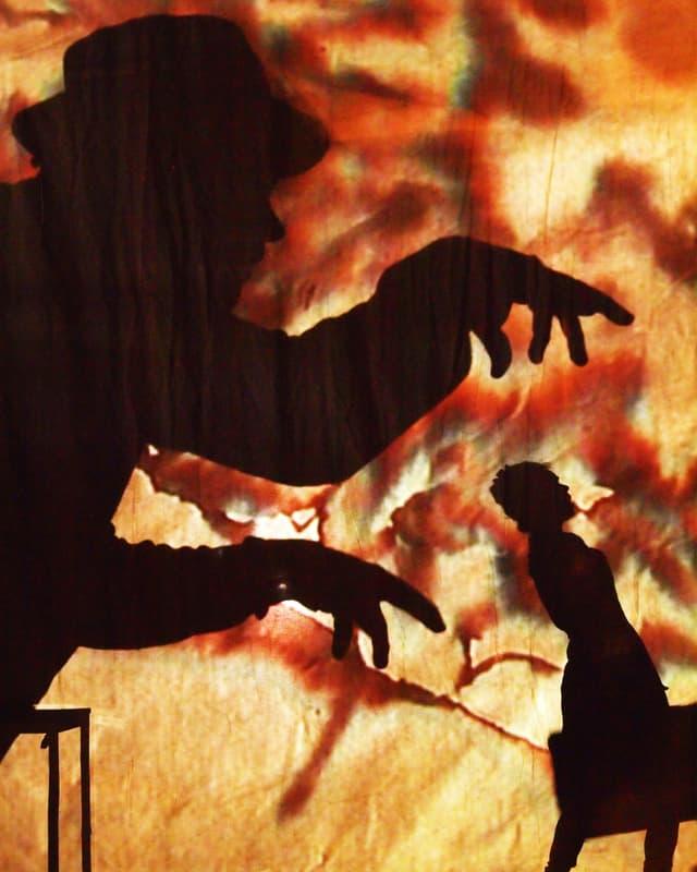 Als Schatten ist ein Mann zu sehen, der mit gekrallten Fingern einer gehenden Passantin nachstellt.