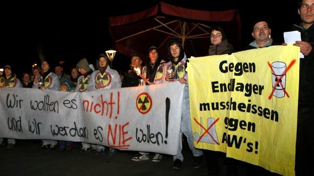 """Gruppe mit Plakaten mit den Aufschriften """"Wir wollen es nicht! Und wir werden es nie wollen!"""" sowie """"Gegen Endlager muss heissen gegen AKWs"""""""