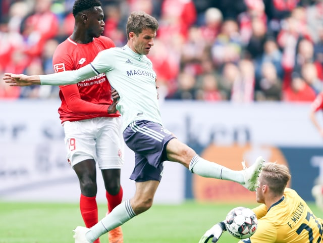 Mainz-Goalie klärt knapp vor dem heranbrausenden Thomas Müller.