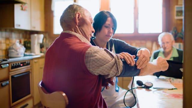 Eine Spitexmitarbeiterin misst den Blutdruck eines Patienten