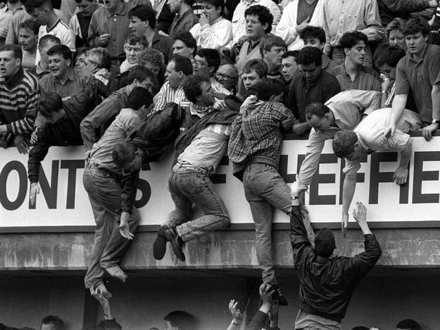 Fans klettern aus dem unteren Block in den Oberrang. (Schwarz-Weiss)