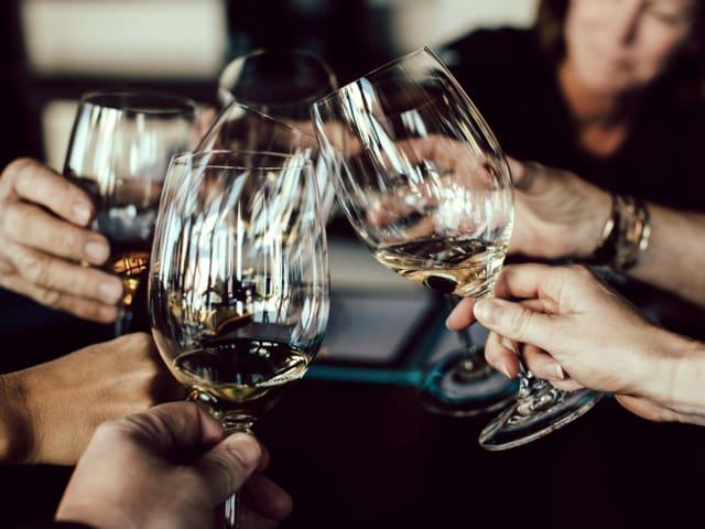 Vier Menschen stossen mit Weingläsern an.