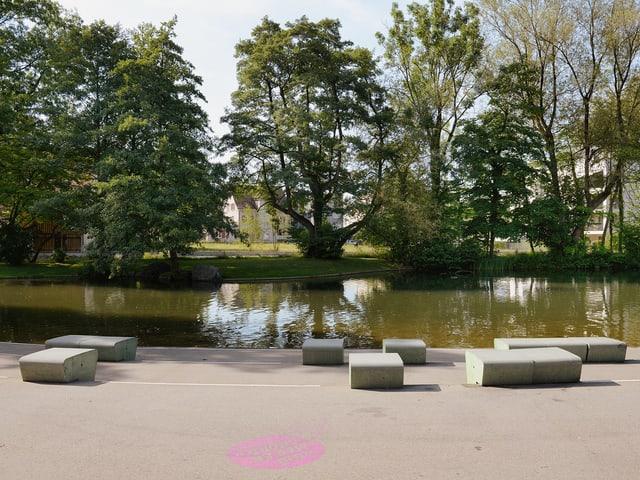 Skulpturale Sitzgelegenheiten vor einem Weiher. Sie sind von Schweingruber Zulauf Landschaftsarchitekten als Gestaltungselemente im Stadtpark.