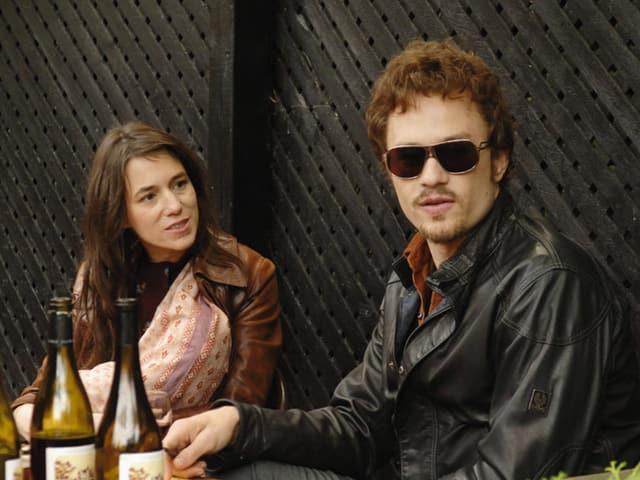 Eine Frau blickt auf einen Mann mit Sonnebrille, auf dem Tisch stehen Weinflaschen.