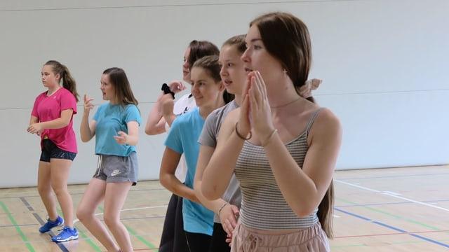 Tanzende jugendliche Mädchen, die in einer Reihe in der Turnhalle stehen.