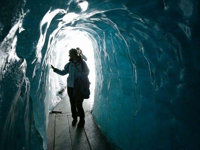 In einer Gletscherhöhle leuchtet das Eis bläulich, eine Frau berührt das Eis in der Höhle mit den Fingern, am Boden ist ein Steg aus Holz ausgelegt.