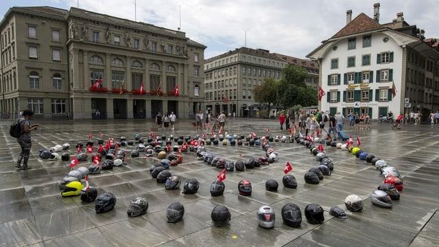 Töff-Helme liegen kreisförmig auf dem Bundesplatz verteilt.