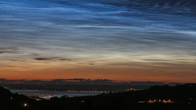 Blick zum Bodensee, darüber das Abendrot mit dunklen Cirren, darüber die bläulich-weissen Leuchtenden Nachtwolken.