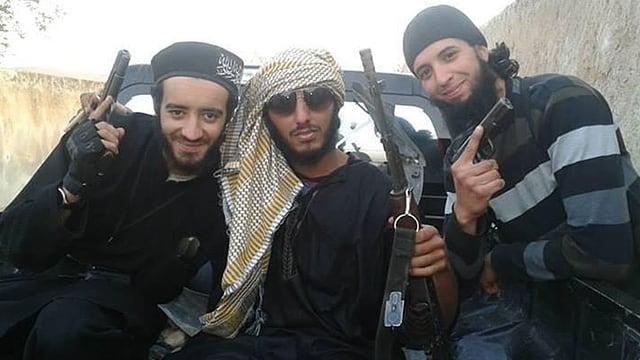 Drei dunkel gekleidete Männer mit Waffen.