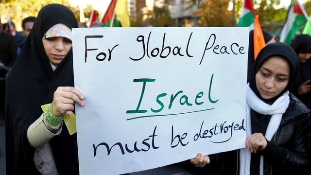 Zwei Frauen halten ein Plakat mit der Aufschrift «For global peace, Israel must be destroyed».