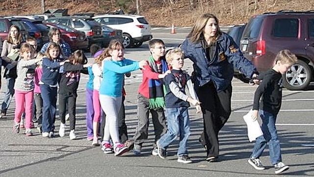Kinder über Parkplatz gehend, von Polizistin begleitend