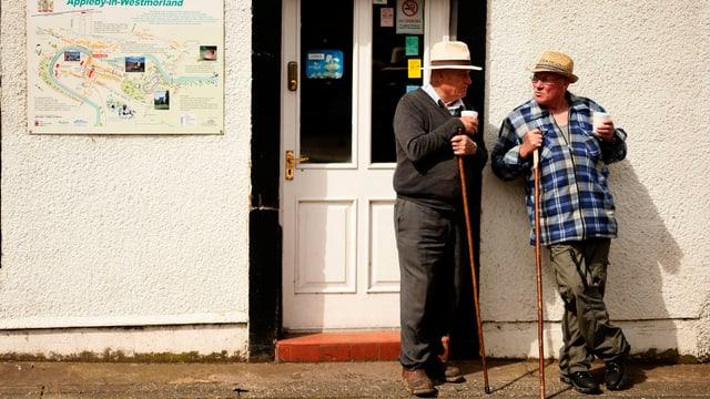 Zwei Männer mit Trinkbecher und Stock an Wand gelehnt