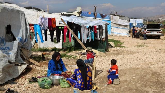 Zwei Frauen sitzen auf dem Boden und bereiten Essen vor, daneben sitzen zwei Kinder. Im Hintergrund hängt Wäsche an einem Seil und man sieht weisse, improvisierte Zelte.