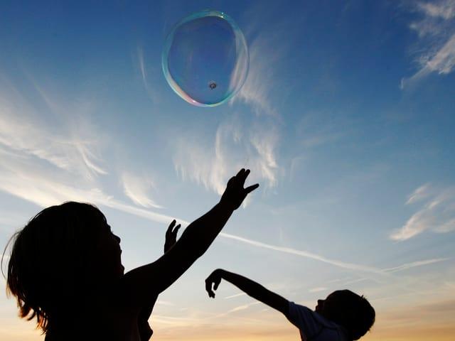 Zwei Kinder - über ihnen fliegt eine Seifenblase