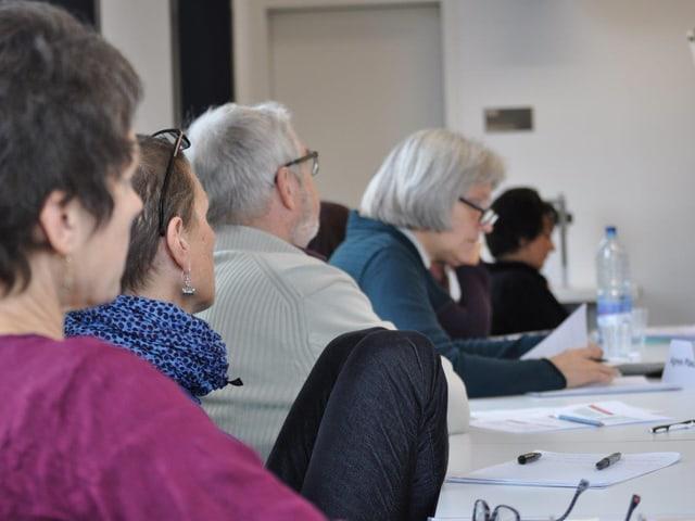 Teilnehmer des Kurses hören zu.