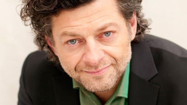 Grossaufnahme des Schauspielers Serkis: Der dunkelhaarige Mann schaut freundlich in die Kamera. Er trägt ein grünes Hemd unter einem schwarzen Jacket.