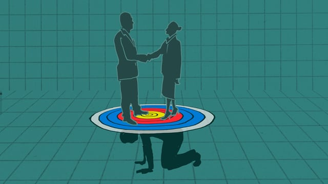 Person kniet am Boden mit Zielscheibe auf dem Rücken, auf der zwei Personen stehen