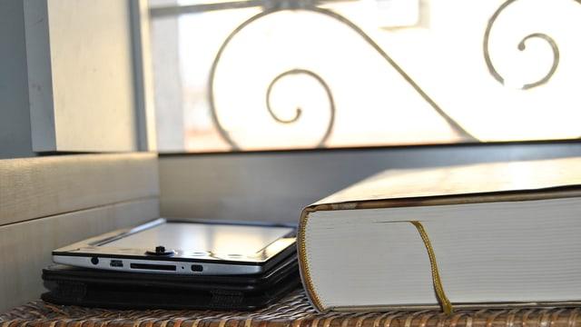 Das Bild zeigt ein dickes Buch und einen E-Reader