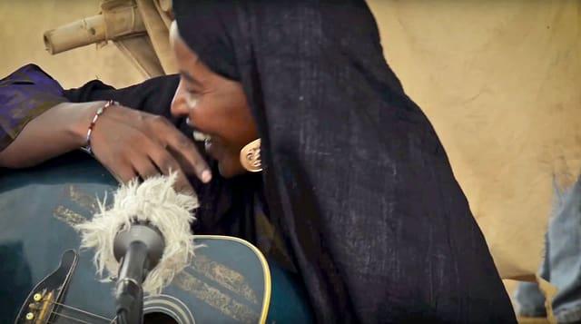 Afrikanische Frau mit Gitarre und Mikrofon.