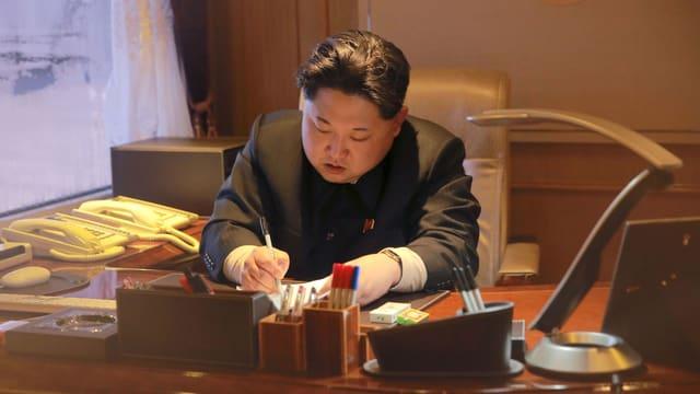 Nordkoreas Führer Kim Jong Un unterzeichnet Dokumente am Schreibtisch.