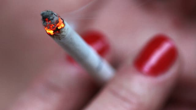 Eine glühende Zigarette zwischen Fingern mit rotlackierten Nägeln.