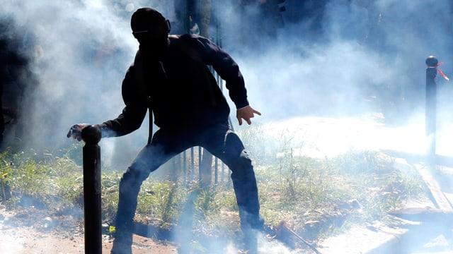 Ein vermummter Jugendlicher in Paris wirft am 1. Mai einen Gegenstand. Um ihn herum ist Rauch zu sehen.