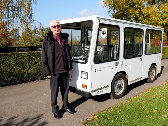Marc Lüthi steht neben einem weissen Elektrobus.