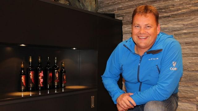 Diego Mathier steht vor ein paar Weinflaschen.