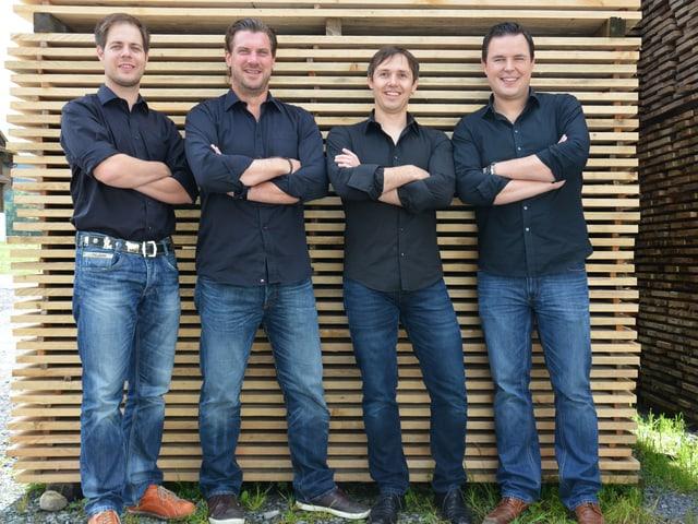 Die vier Musiker tragen Jeans und dunkelblaue Hemden und stehen vor einem Stapel Holzbrettern.