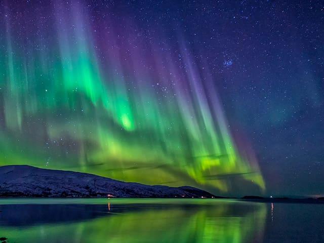 Der Blick geht von einem See her über die glatte Wasseroberfläche zum Land. Über dem Ufer am Sternenhimmel ist farbiges Polarlicht in Säulen zu sehen. Violett, grün bis gelb.