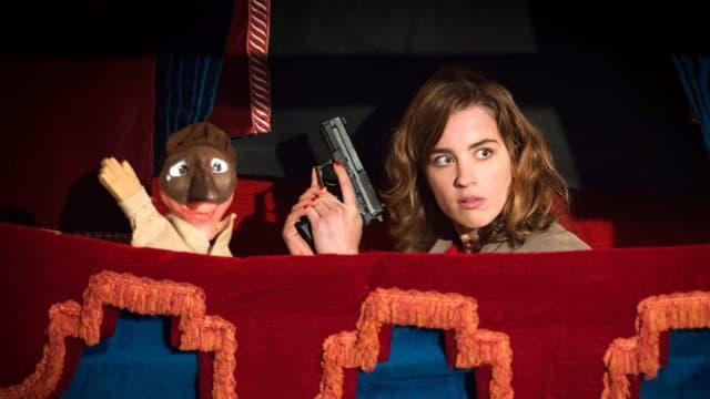 Frau mit Pistole und Gangster-Handpuppe in einem Puppentheater