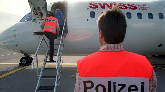 Polizei begleitet Menschen ins Flugzeug.