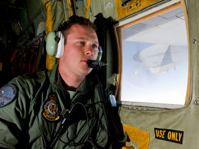 Ein Mann mit Kopfhörern sitzt an einem Fenster in einer Militärmaschine