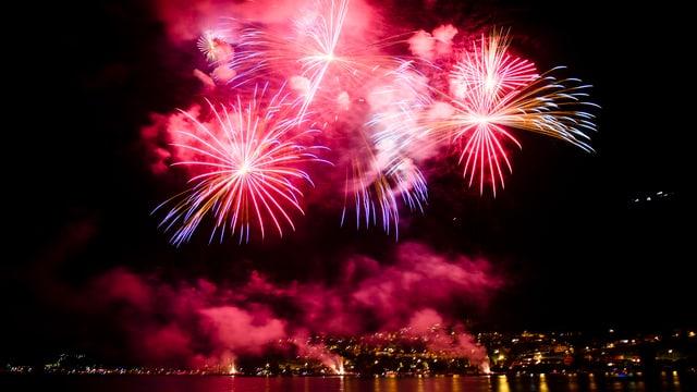 Feuerwerk an Nachthimmel über einem See.