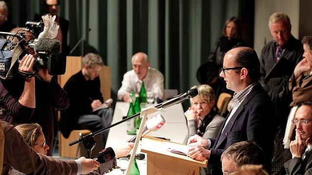 Ein steht mit Mikrofon vor Publikum