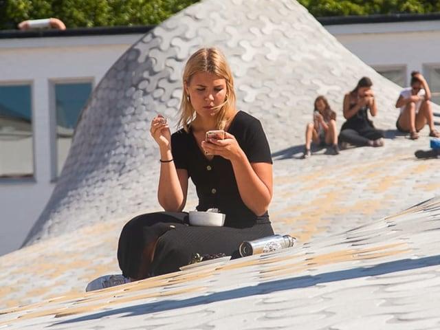Eine junge Frau sitzt am Boden und schaut in ihr Smartphone.
