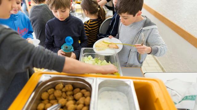 Schüler stehen Schlange für Essen in einer Tagesschule.