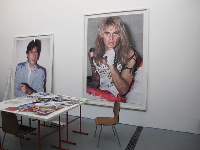 Arbeitstisch im Atelier, an der Wand gross aufgezogene Fotografien von Hannes Schmid.