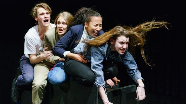Vier Jugendliche sitzen hintereinander, halten sich fest und schreien