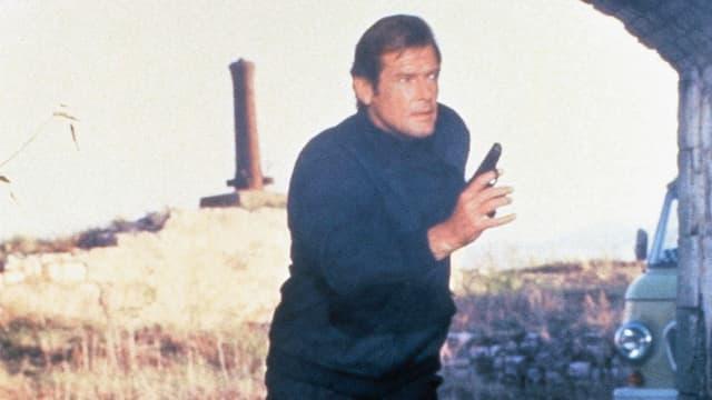 Roger Moore als James Bond verfolgt jemanden mit gezückter Pistole.