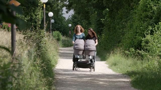 zwei Frauen stossen draussen einen Kinderwagen