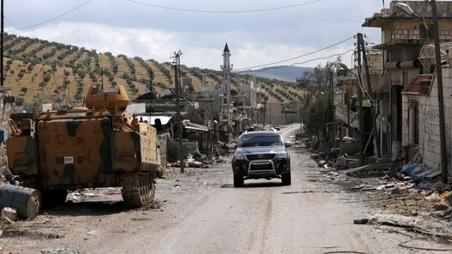 Panzer und Auto auf einer Strasse, daneben beschädigte Häuser, im Hintergrund Olivenplantagen.