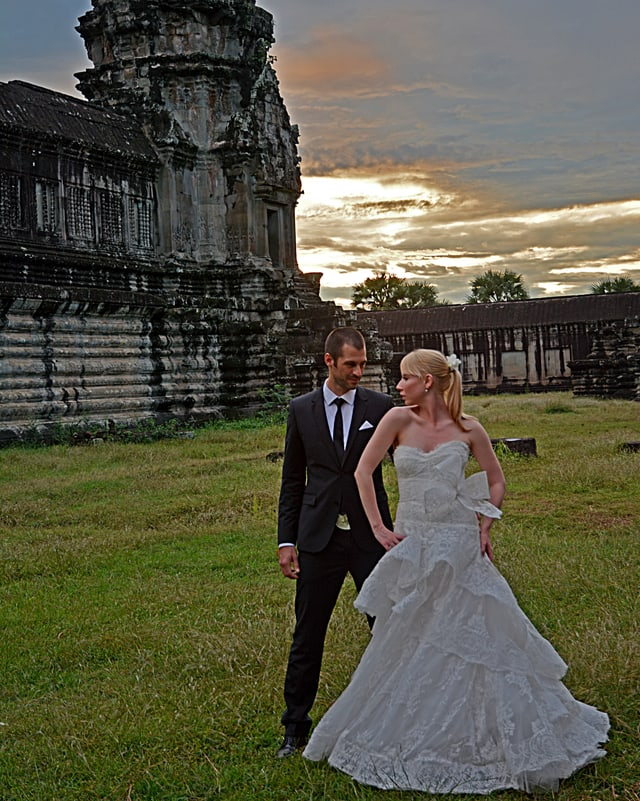 Patrick und Ashley Kerber vor einer alten Tempelanlage in Hochzeitskleidern.